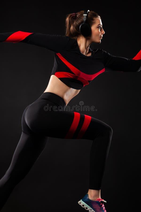 Ισχυρή αθλητική γυναίκα sprinter, τρέχοντας στο μαύρο υπόβαθρο που φορά sportswear και τα ακουστικά o στοκ φωτογραφίες