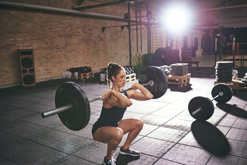 Ισχυρή γυναίκα που κάθεται οκλαδόν με ένα βαρύ barbell στοκ εικόνες