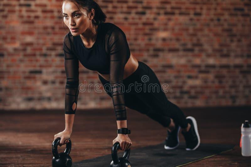 Ισχυρή γυναίκα που κάνει το ώθηση-UPS στο κουδούνι κατσαρολών στοκ εικόνες