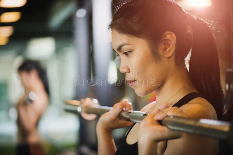 Ισχυρή νέα ασιατική γυναίκα με να κάνει τις ασκήσεις με το barbell στοκ εικόνες