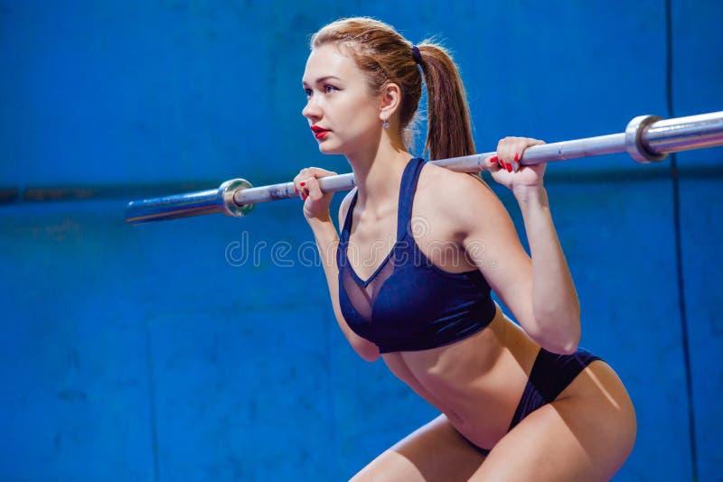 Ισχυρή νέα γυναίκα με το όμορφο αθλητικό σώμα που κάνει τις ασκήσεις με το barbell Ικανότητα, η υγεία προσοχής όπλων απομόνωσε τι στοκ φωτογραφία με δικαίωμα ελεύθερης χρήσης