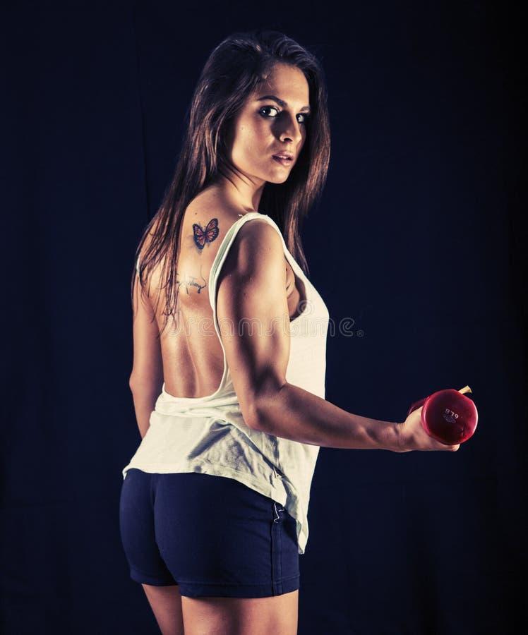 Ισχυρή νέα γυναίκα που κάνει bicep τις μπούκλες στοκ φωτογραφία με δικαίωμα ελεύθερης χρήσης