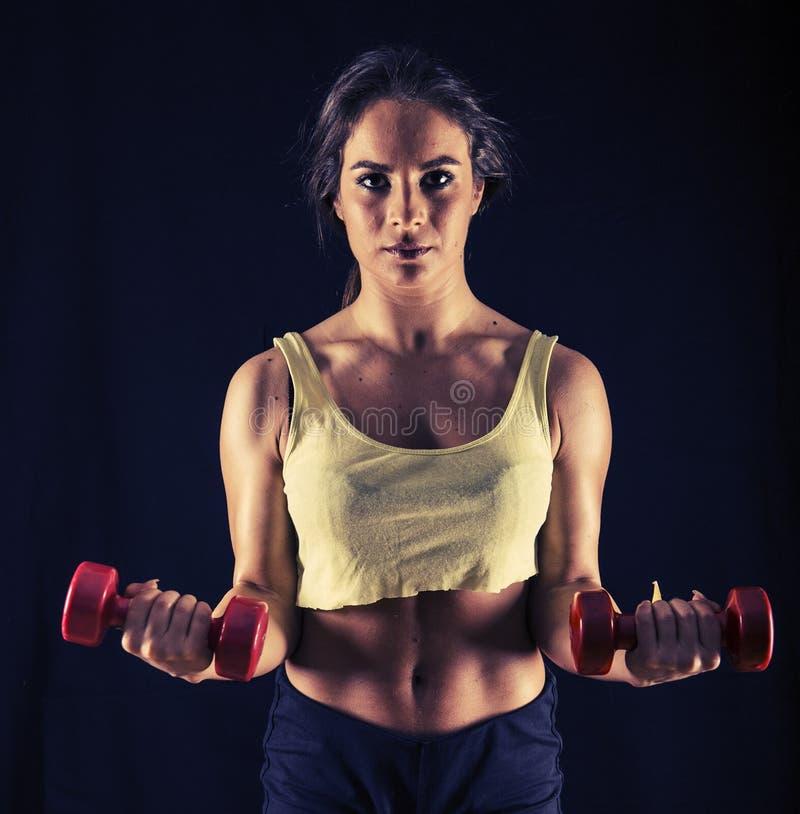 Ισχυρή νέα γυναίκα που κάνει bicep τις μπούκλες στοκ εικόνα