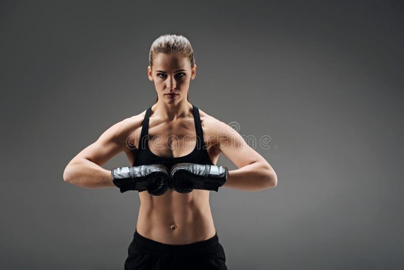 Ισχυρή τοποθέτηση γυναικών με τα εγκιβωτίζοντας γάντια στοκ εικόνα