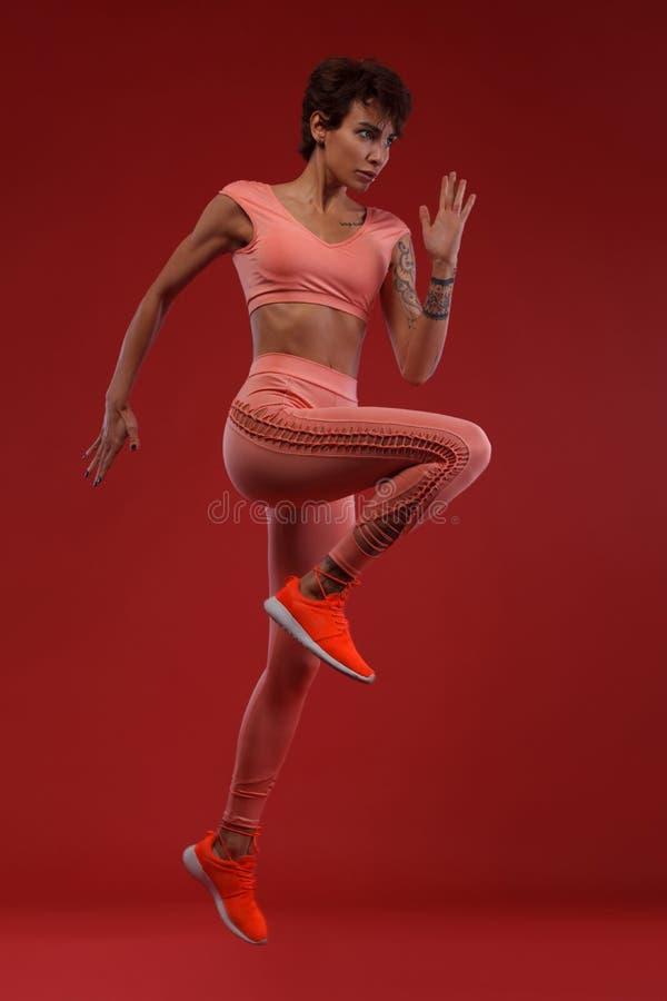 Ισχυρός ένας αθλητικός, γυναίκα sprinter ή δρομέας, που τρέχει στο κόκκινο υπόβαθρο που φορά sportswear Ικανότητα και αθλητικό κί στοκ φωτογραφία με δικαίωμα ελεύθερης χρήσης