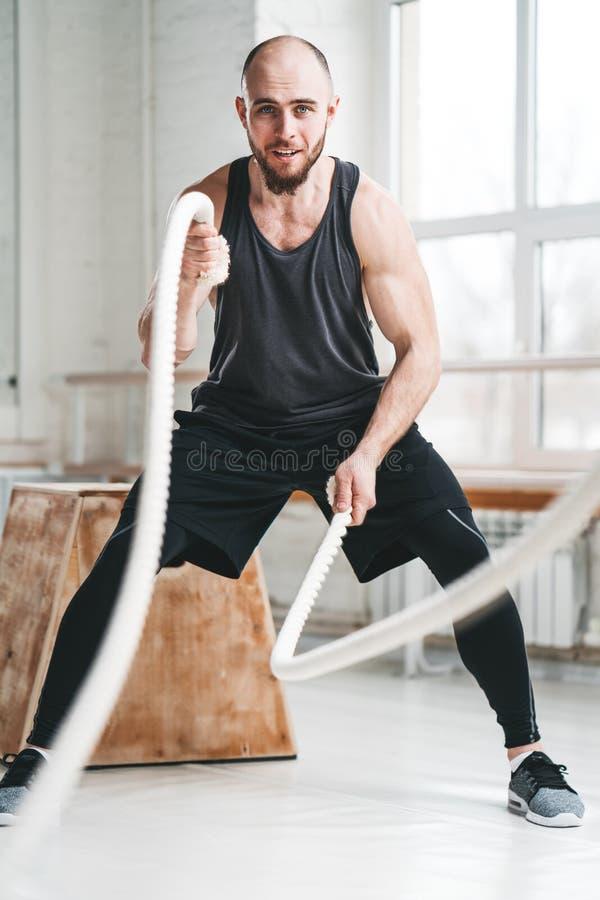 Ισχυρός αθλητικός τύπος ικανότητας που χρησιμοποιεί τα σχοινιά κατάρτισης για την άσκηση στη γυμναστική στοκ εικόνες
