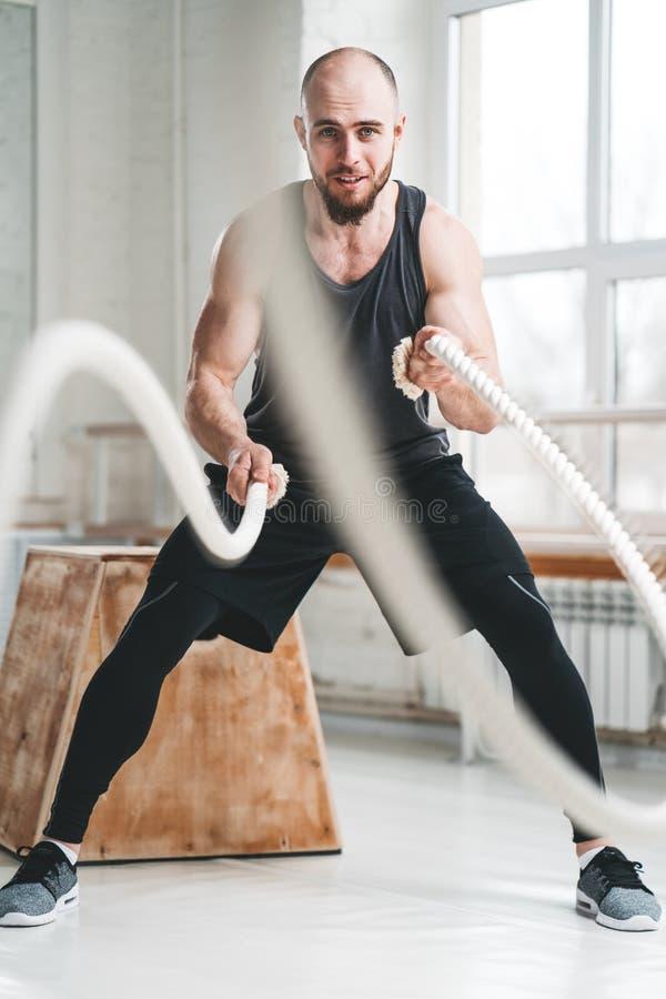 Ισχυρός αρσενικός αθλητής που κάνει τις ασκήσεις με το σχοινί στη γυμναστική crossfit στοκ φωτογραφία με δικαίωμα ελεύθερης χρήσης