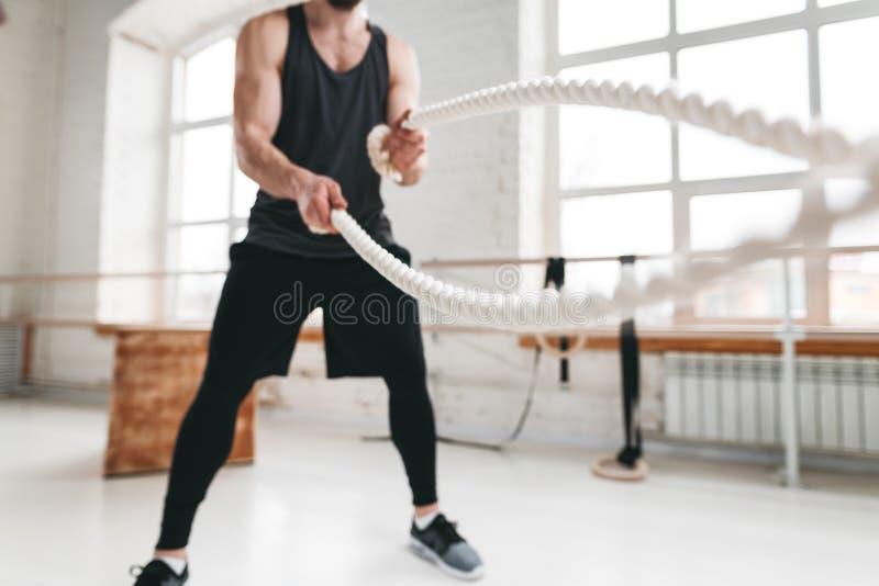 Ισχυρός αρσενικός αθλητής που κάνει τις ασκήσεις με το σχοινί στη γυμναστική crossfit στοκ φωτογραφίες