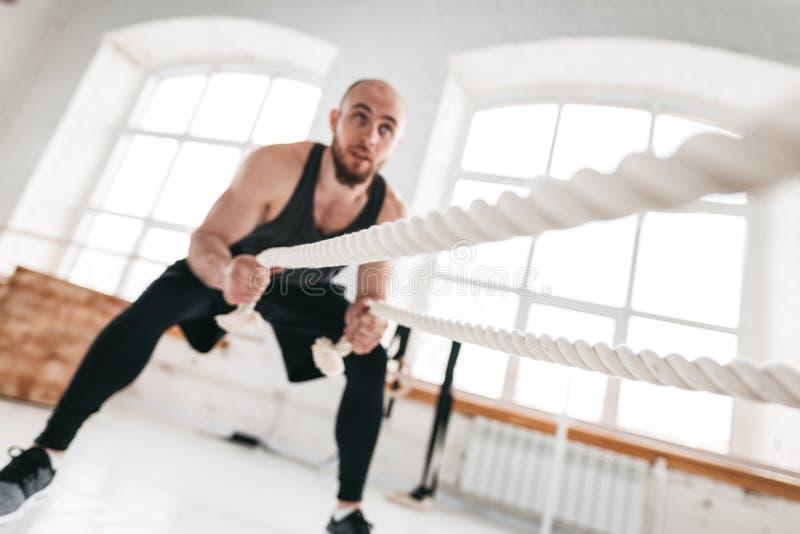 Ισχυρός αρσενικός αθλητής που κάνει τις ασκήσεις με το σχοινί στη γυμναστική crossfit στοκ εικόνα με δικαίωμα ελεύθερης χρήσης