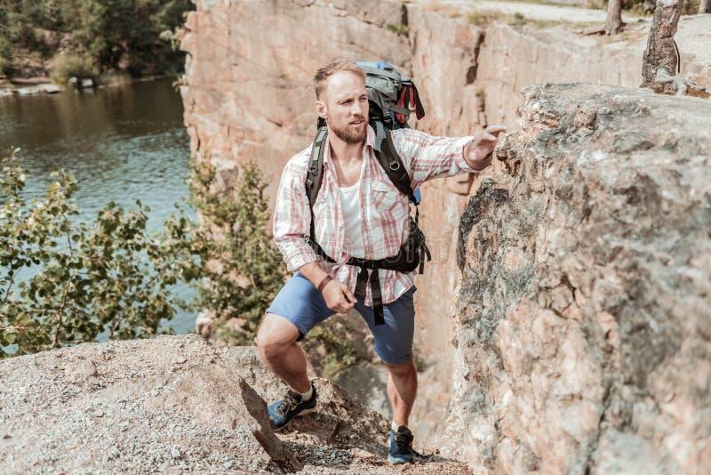Ισχυρός γενειοφόρος ξανθός-μαλλιαρός οδοιπόρος που κρατά το βαρύ σακίδιο πλάτης πεζοποριες κοντά στη λίμνη στοκ φωτογραφία με δικαίωμα ελεύθερης χρήσης