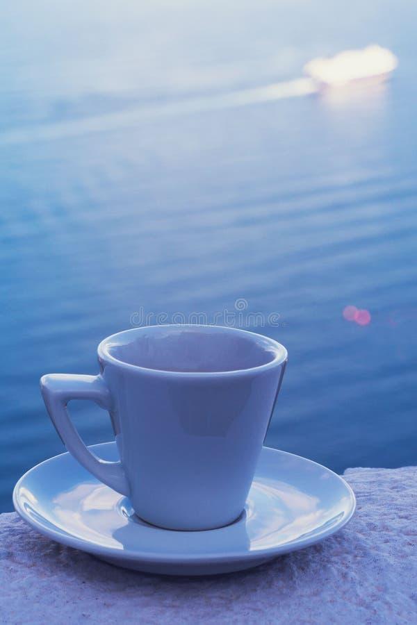 Ισχυρός εύγευστος καφές σε ένα άσπρο φλυτζάνι με ένα πιατάκι ενάντια στο σκηνικό της θάλασσας και ενός επιπλέοντος σκάφους της γρ στοκ φωτογραφία με δικαίωμα ελεύθερης χρήσης
