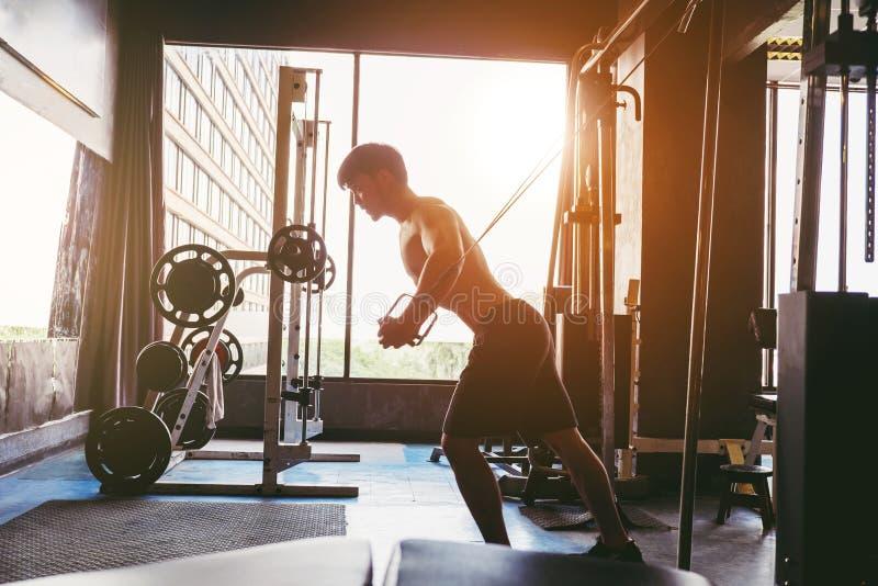 Ισχυρό άτομο ικανότητας που κάνει τη βαρέων βαρών άσκηση στη μηχανή στη γυμναστική στοκ εικόνα