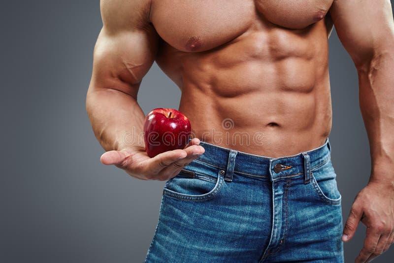 Ισχυρό άτομο μυών που κρατά την κόκκινη Apple στοκ εικόνες