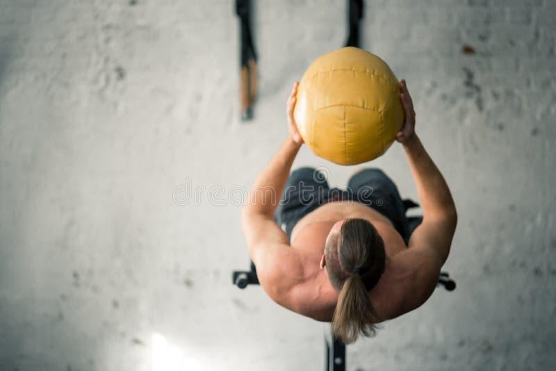 Ισχυρό αθλητικό άτομο που εκτελεί την άσκηση ABS με τη σφαίρα ιατρικής στοκ φωτογραφίες με δικαίωμα ελεύθερης χρήσης