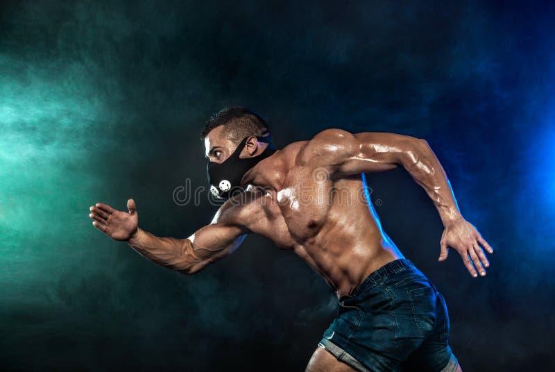 Ισχυρό αθλητικό άτομο sprinter στη μάσκα κατάρτισης, τρέξιμο, ικανότητα και αθλητικό κίνητρο Έννοια δρομέων με το διάστημα αντιγρ στοκ εικόνες