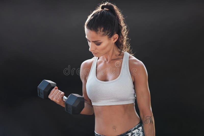 Ισχυρό και μυϊκό θηλυκό που ασκεί με τον αλτήρα στοκ φωτογραφία με δικαίωμα ελεύθερης χρήσης