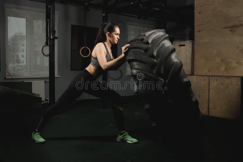 Ισχυρό κορίτσι που κτυπά μια ρόδα στη γυμναστική στοκ εικόνες