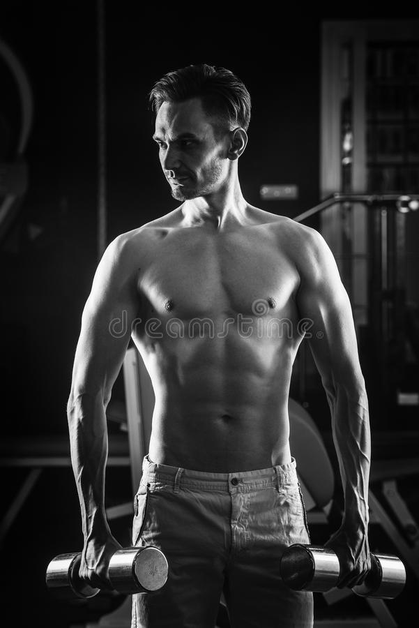 Ισχυρό μυϊκό άτομο με τα γυμνά ABS κορμών που επιλύει στη γυμναστική με τα dumbells Γραπτή φωτογραφία του Πεκίνου, Κίνα στοκ εικόνες