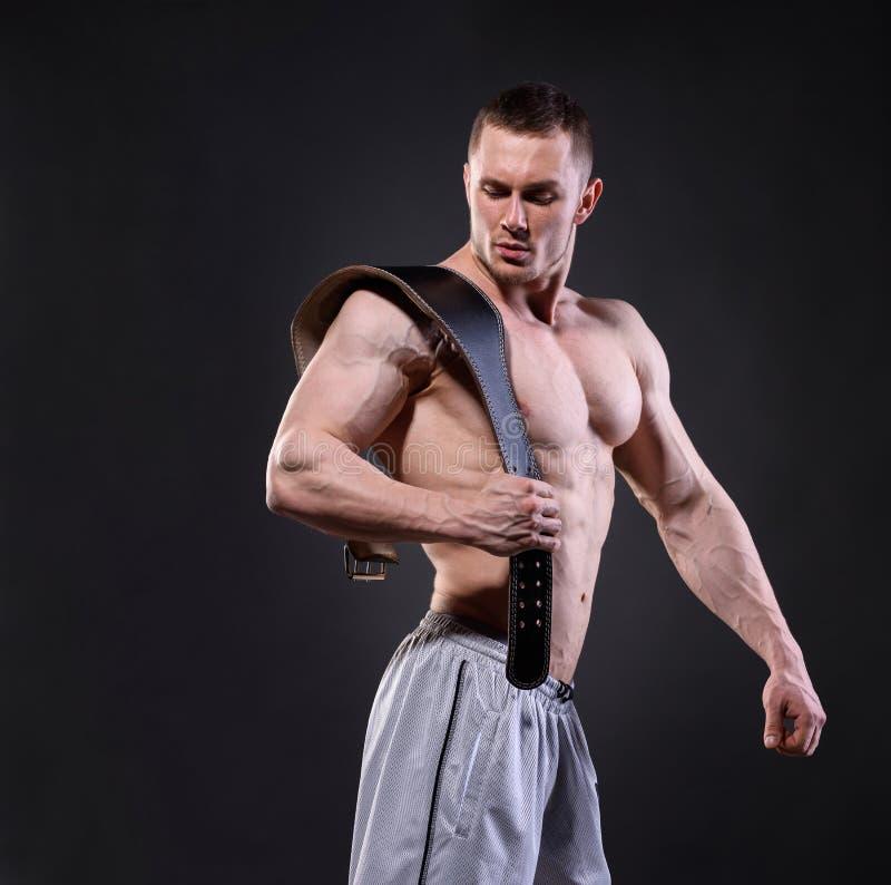 Ισχυρό μυϊκό άτομο με την ανύψωση της τοποθέτησης ζωνών πέρα από το σκοτεινό backgroun στοκ εικόνες