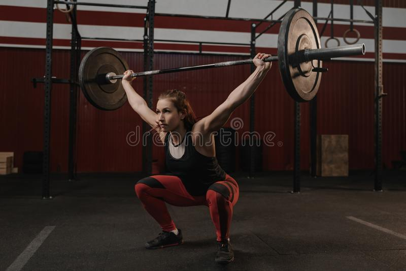Ισχυρό να κάνει αθλητριών κάθεται οκλαδόν με το βαρύ barbell από πάνω στη γυμναστική crossfit στοκ φωτογραφία με δικαίωμα ελεύθερης χρήσης