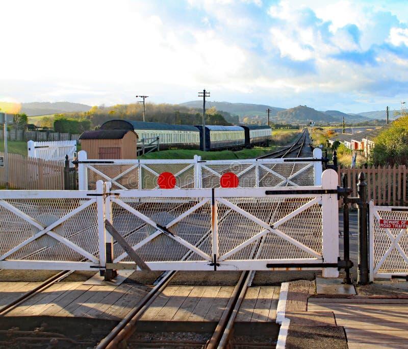 Ισόπεδο πέρασμα με την πλατφόρμα σταθμών στο σιδηρόδρομο κληρονομιάς δυτικού Somerset στην μπλε άγκυρα στοκ εικόνες