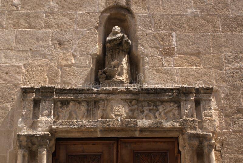 Ιταλία, το νησί της Σαρδηνίας Η πόλη Alghero Μια αρχαία εκκλησία στην παλαιά μεσαιωνική πόλη Ένα χαρασμένο πλαίσιο σε μια πόρτα στοκ εικόνα