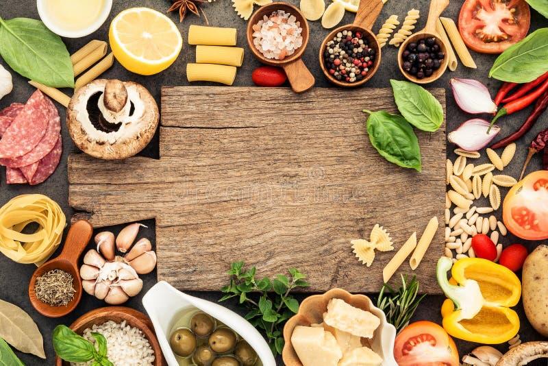 Ιταλικά μαγειρεύοντας συστατικά τροφίμων στο σκοτεινό υπόβαθρο πετρών με το γ στοκ εικόνα με δικαίωμα ελεύθερης χρήσης