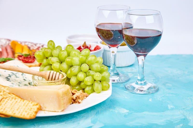 Ιταλικά πρόχειρα φαγητά κρασιού antipasti καθορισμένα Brushettas στο μπλε υπόβαθρο στοκ φωτογραφία με δικαίωμα ελεύθερης χρήσης