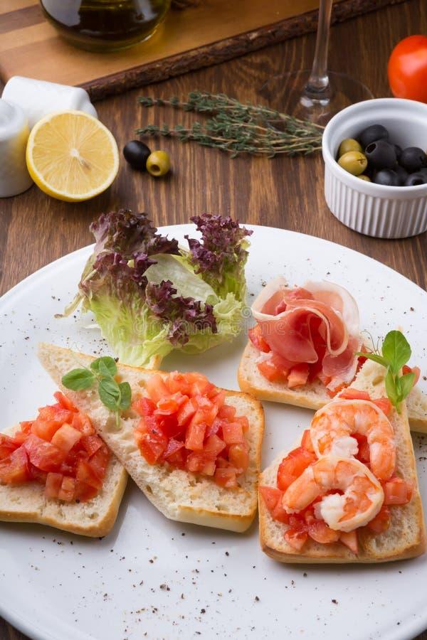 Ιταλικά σάντουιτς Bruschetta με τις ντομάτες, το μπέϊκον, και τις γαρίδες στοκ φωτογραφία με δικαίωμα ελεύθερης χρήσης