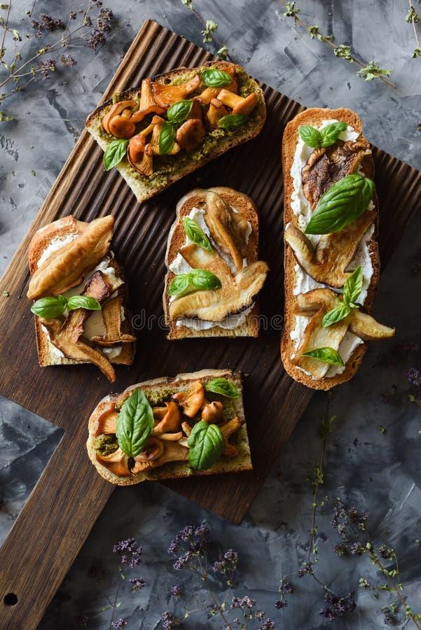 Ιταλικά σπιτικά σάντουιτς με τα δασικά μανιτάρια Τηγανισμένα chanterelles και μανιτάρια porcini με το βασιλικό στο bruschetta στο στοκ φωτογραφία