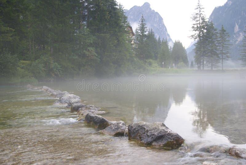 Ιταλική λίμνη της Misty που διατρέχει των βράχων στοκ εικόνα