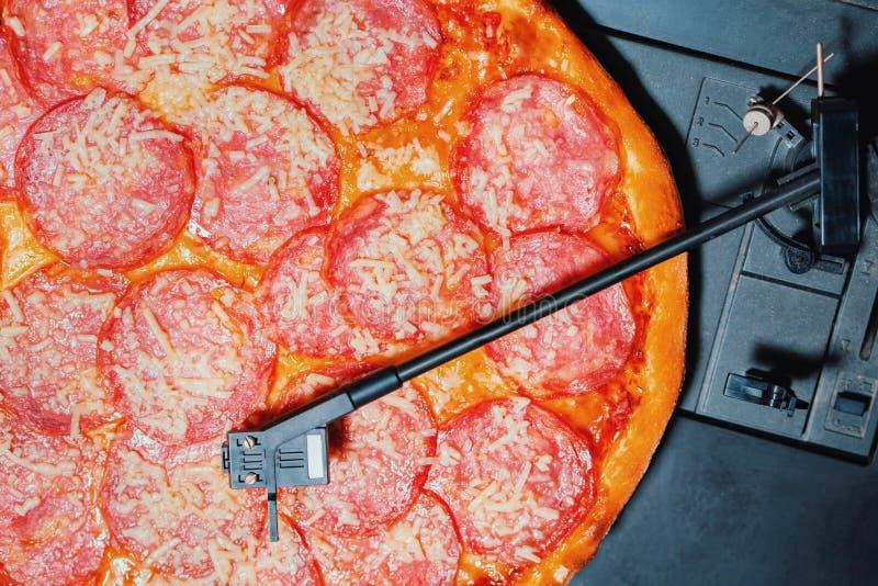 Ιταλική πίτσα με το σαλάμι ως βινυλίου αρχείο που περιστρέφεται στο φορέα περιστροφικών πλακών Pepperoni, έννοια του κόμματος με  στοκ φωτογραφίες με δικαίωμα ελεύθερης χρήσης