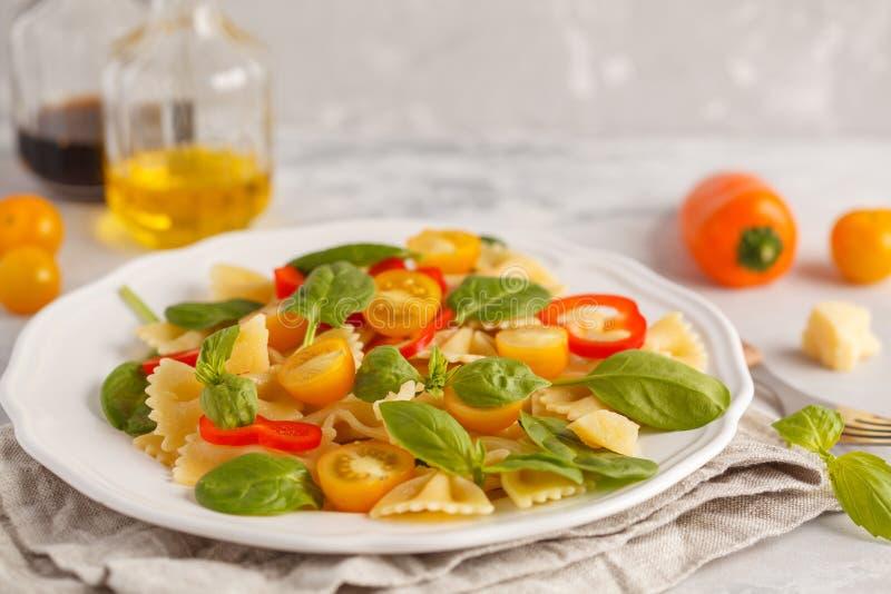 Ιταλική σαλάτα ζυμαρικών farfalle με τα λαχανικά, το βασιλικό και το σπανάκι στοκ εικόνα