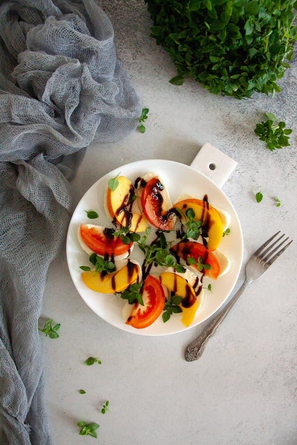 Ιταλική σαλάτα με τη μοτσαρέλα, την ντομάτα, το ροδάκινο και το βασιλικό στοκ εικόνες