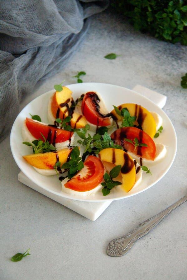 Ιταλική σαλάτα με τη μοτσαρέλα, την ντομάτα, το ροδάκινο και το βασιλικό στοκ φωτογραφίες με δικαίωμα ελεύθερης χρήσης