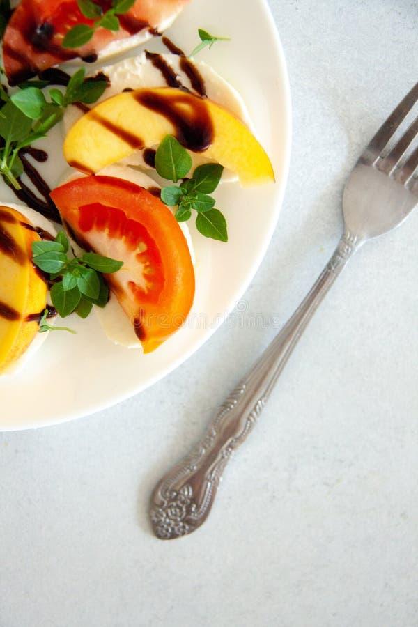 Ιταλική σαλάτα με τη μοτσαρέλα, την ντομάτα, το ροδάκινο και το βασιλικό στοκ εικόνες με δικαίωμα ελεύθερης χρήσης