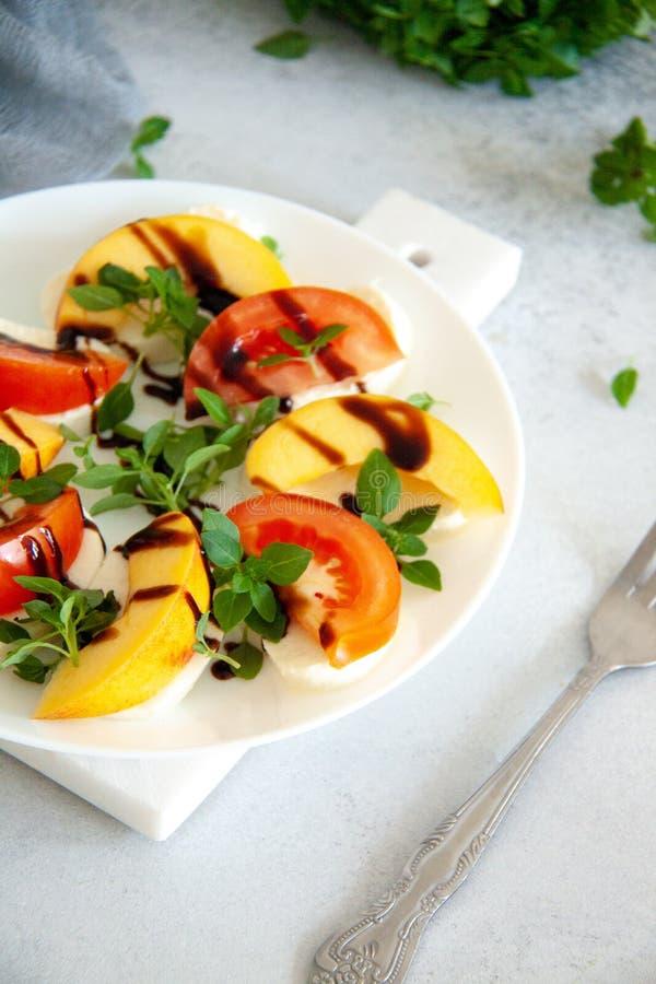 Ιταλική σαλάτα με τη μοτσαρέλα, την ντομάτα, το ροδάκινο και το βασιλικό στοκ εικόνα με δικαίωμα ελεύθερης χρήσης