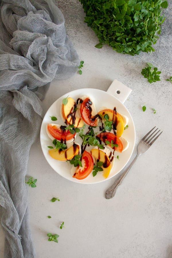 Ιταλική σαλάτα με τη μοτσαρέλα, την ντομάτα, το ροδάκινο και το βασιλικό στοκ φωτογραφία