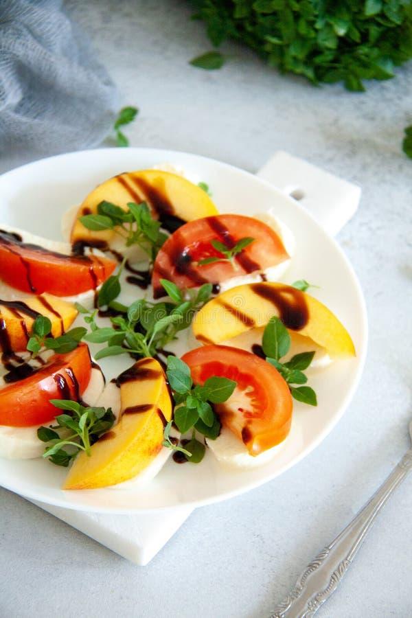 Ιταλική σαλάτα με τη μοτσαρέλα, την ντομάτα, το ροδάκινο και το βασιλικό στοκ φωτογραφία με δικαίωμα ελεύθερης χρήσης