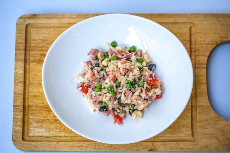 Ιταλική σαλάτα ρυζιού ή κρύο ρύζι σε ένα άσπρο πιάτο σε έναν τεμαχίζοντας πίνακα με το θολωμένο άσπρο υπόβαθρο στοκ φωτογραφία με δικαίωμα ελεύθερης χρήσης