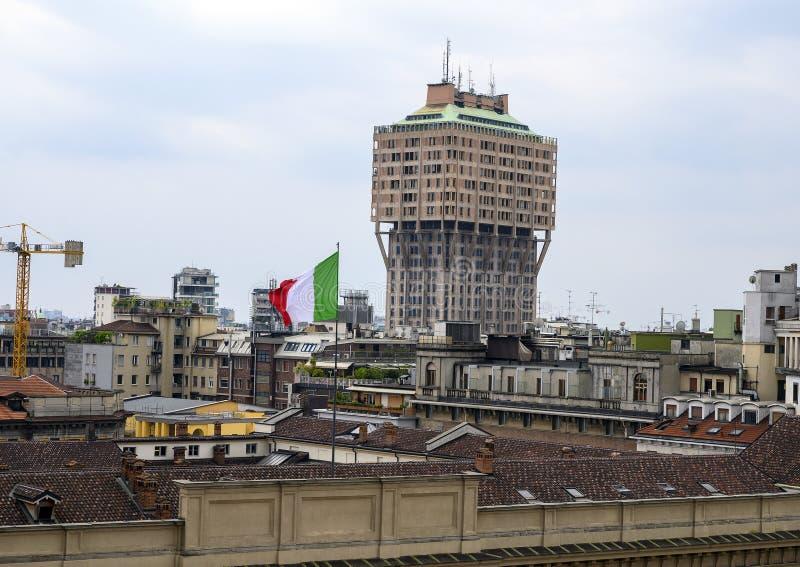 Ιταλική σημαία επάνω στη Royal Palace και ο ορίζοντας του Μιλάνου όπως αντιμετωπίζεται από τη στέγη του καθεδρικού ναού του Μιλάν στοκ φωτογραφία