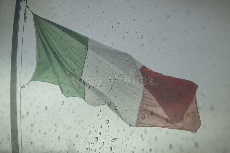 Ιταλική σημαία κάτω από τις λυπημένες πτώσεις βροχής στοκ φωτογραφίες