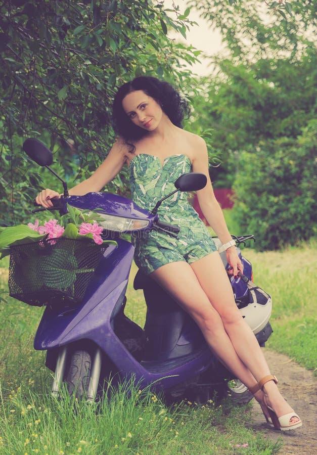 Ιταλικό ύφος Όμορφο νέο κορίτσι που οδηγά ένα μηχανικό δίκυκλο στοκ εικόνες