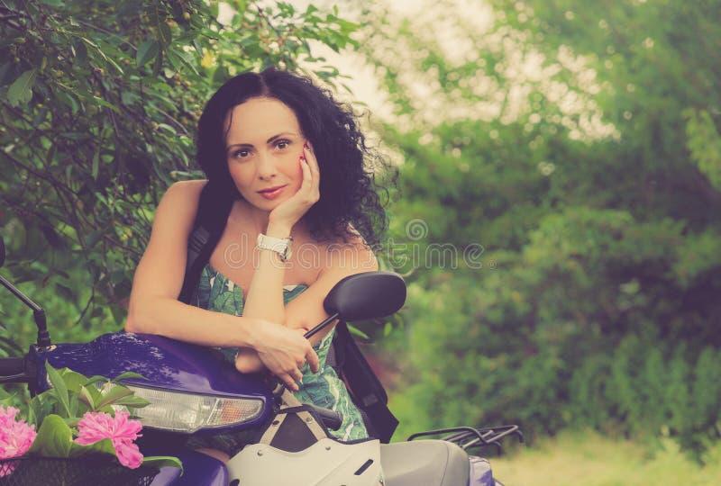 Ιταλικό ύφος Όμορφο νέο κορίτσι που οδηγά ένα μηχανικό δίκυκλο στοκ φωτογραφία με δικαίωμα ελεύθερης χρήσης