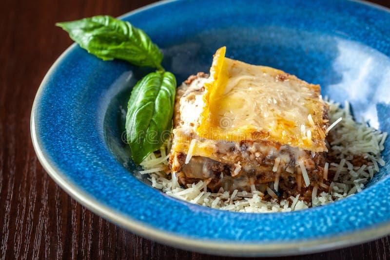 Ιταλικό lasagna με τον κιμά bolognese, τα καρότα, και το τυρί παρμεζάνας σε ένα όμορφο κεραμικό μπλε πιάτο Διάστημα αντιγράφων, ε στοκ φωτογραφίες