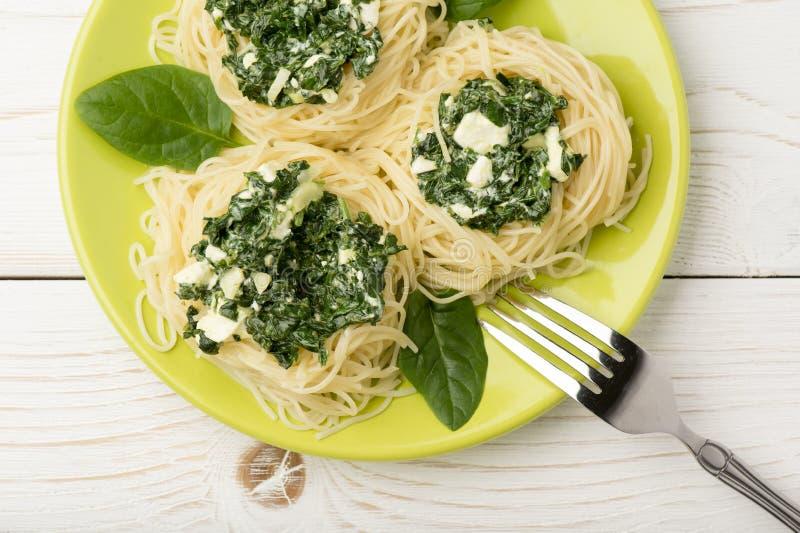 Ιταλικά ζυμαρικά με το σπανάκι και φέτα στο πράσινο πιάτο στο ξύλινο υπόβαθρο στοκ εικόνα με δικαίωμα ελεύθερης χρήσης
