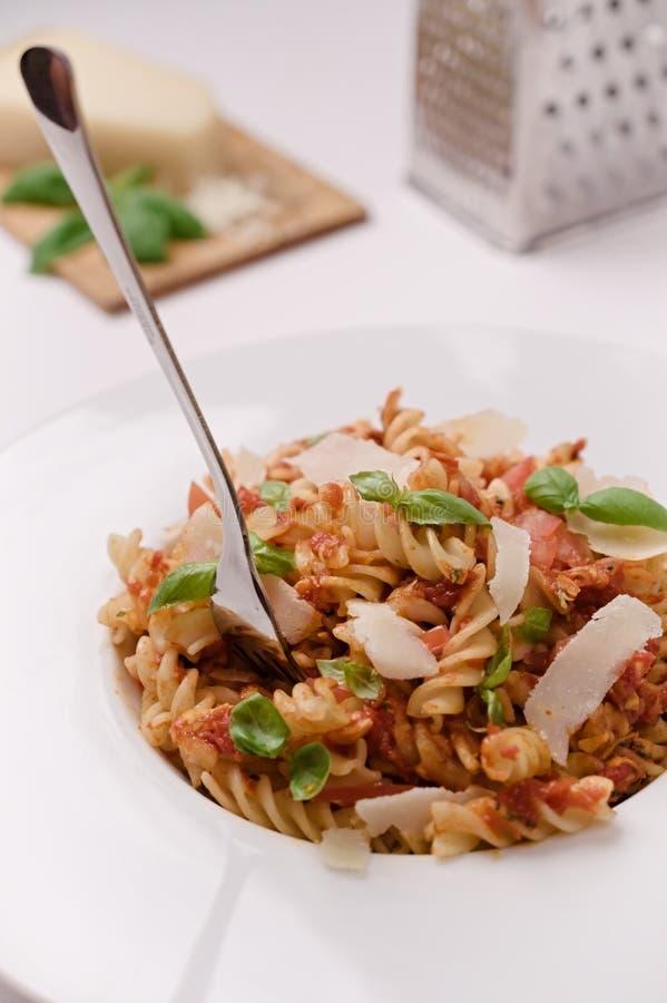Ιταλικά ζυμαρικά fusilli με τη σάλτσα ντοματών, το βασιλικό και το chee παρμεζάνας στοκ εικόνες