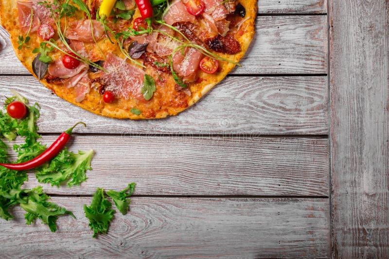 Ιταλική πίτσα σε ένα αγροτικό επιτραπέζιο υπόβαθρο, κινηματογράφηση σε πρώτο πλάνο Ένα δεύτερο της πίτσας κρέατος με τα φύλλα σαλ στοκ φωτογραφίες με δικαίωμα ελεύθερης χρήσης