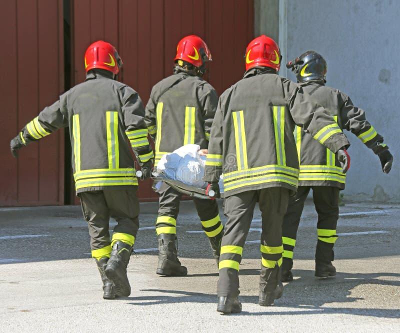 Ιταλικοί πυροσβέστες με ΤΡΑΥΜΑΤΙΣΜΕΝΟΣ στοκ φωτογραφίες με δικαίωμα ελεύθερης χρήσης