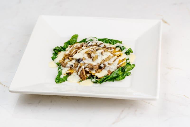 Ιταλικό ravioli με τα φρέσκα ψημένα μανιτάρια και την κρεμώδη σάλτσα τυριών παρμεζάνας που διακοσμούνται με το σπανάκι στο άσπρο  στοκ εικόνες με δικαίωμα ελεύθερης χρήσης